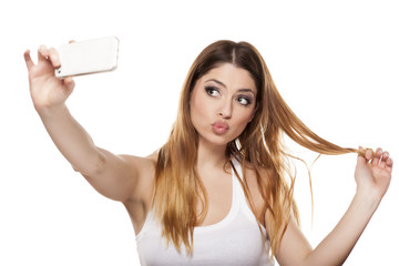 Attractive young woman is taking a selfie