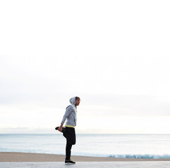 Young athletic man doing stretches next to the beach at morning