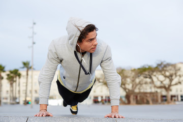 Cross-training at early morning outdoors, man doing push ups