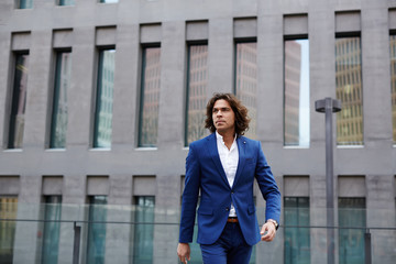 Young businessman in suit looking away while walking in street