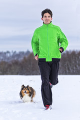 junger Mann joggt mit Hund in verschneiter Winterlandschaft