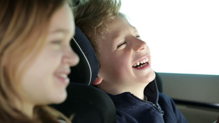 two young, cheerful children who are having fun back in the car, while driving in a car to a certain destination