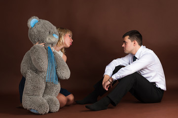 woman take away teddy bear of a young businessman