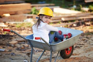 girl riding in the construction wheelbarrow