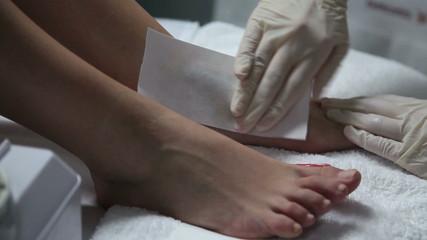 Cosmetician waxing customer's instep