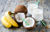 Coconut milk smoothie drink with bananas on wooden background