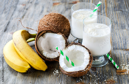 Coconut milk smoothie drink with bananas on wooden background - 77551373