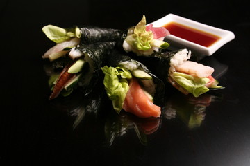 sashimi and rolls on black background