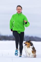 junge Frau joggt mit Hund (Shetland Sheepdog) im Schnee