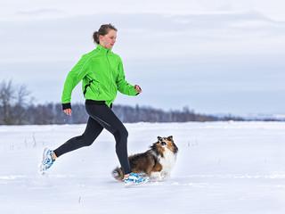 junge Frau joggt mit Hund in verschneiter Winterlandschaft
