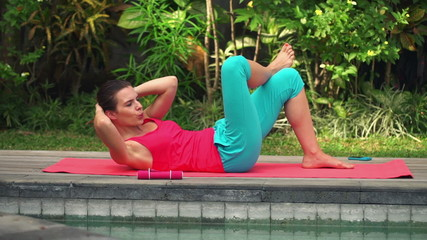 Young attractive woman doing twist sit-ups on mat in garden
