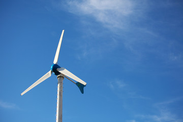Green renewable energy concept - wind generator turbines on blue
