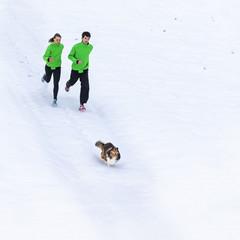 junger Mann und Frau joggen mit Hund in verschneiter Landschaft