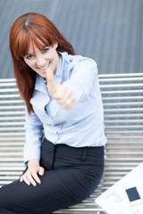 Smiling businesswoman is sitting on a metal bench and making pos