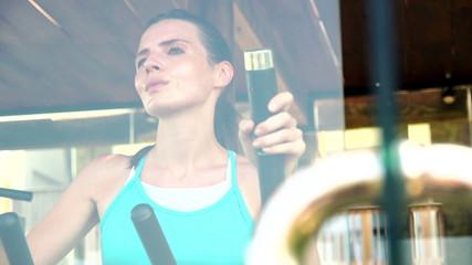 Young, beautiful woman exercising on elliptical machine