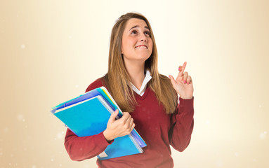 Student with her fingers crossing over white background