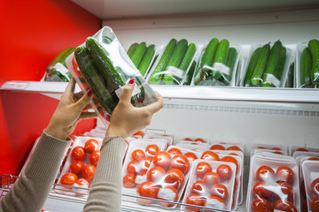 Packaged cucumber with woman hand in the supermarket