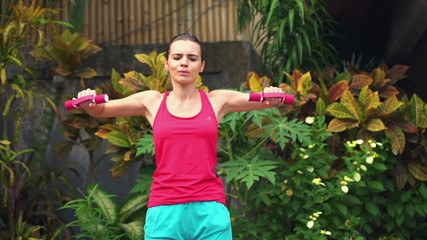Young, beautiful woman exercising with dumbbells in the garden