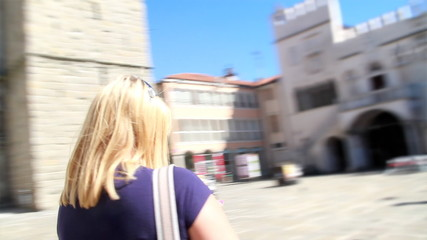 Two beautiful ladies are walking around the old city center, talking and watching architecture