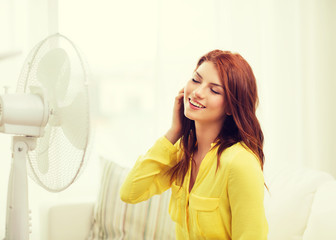smiling redhead teenage girl with big fan at home