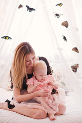 Beautiful young woman with small daughter sitting on bed