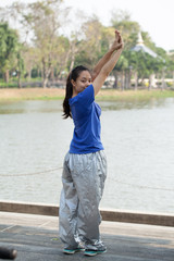 Asia woman warming up before her morning workout in the Garden.