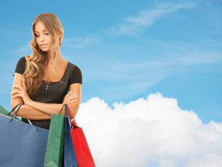 young woman with shopping bags over blue sky