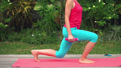 Young woman exercising squat with dumbbells on mat in garden