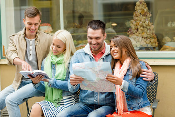 group of friends with guide and map exploring town