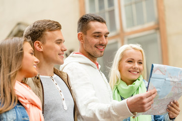 group of friends with map exploring city