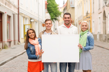 group of smiling friends with blank white board