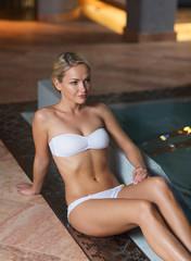 happy woman in bikini sitting at swimming pool