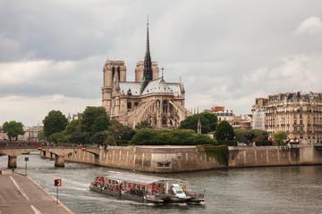 Notre Dame with  tourist boat on Seine in Paris