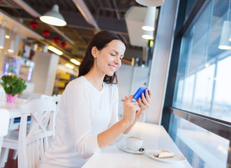 smiling woman with smartphone and coffee at cafe