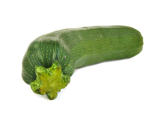 Frontal view of a green and ripe zucchini on white background.