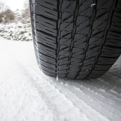 Close up shot of a car's tire in snow at winter