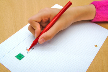 Child drawing a red triangle and a green square with a red wax