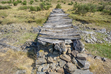 Top of bridge made with wood and stones, dried up stream
