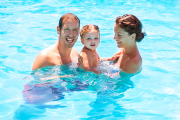 Happy family in swimming pool with baby girl