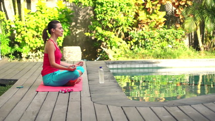 Young woman meditating on mat in garden by swimming pool