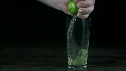 Lime juice pours rapidly into the glass while hand is squezzing the lime