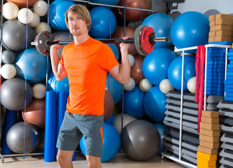 barbell squats blond man at gym exercise