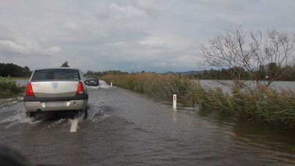 Shot from the car representing flooded country and flooded road with car in the front