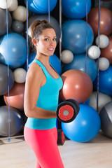 Blue eyes girl at gym weightlifting dumbbells