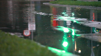 Wiew of the traficlight green reflection in the water