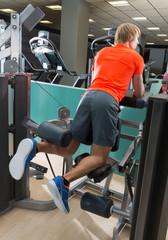 Kneeling leg femoral curl man at gym