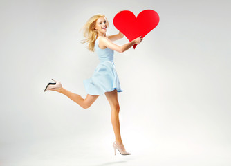 Blond cute lady running with heart