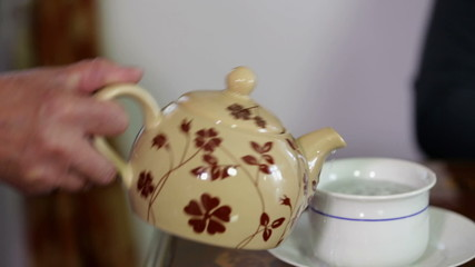 Old lady with shaking hand pouring a tea into a cup