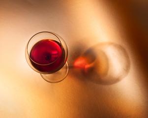 Calice di vino rosso su fondo caldo con ombra.Vista dall'alto