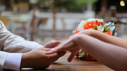 Bride and groom sitting at a table and holding hands